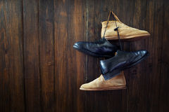 Sistema de botas viejas que cuelgan en el clavo imagenes de archivo