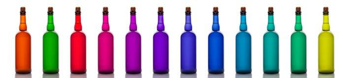 Sistema de botellas de cristal coloreadas, aislado en el fondo blanco Fotografía de archivo libre de regalías