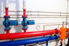 Sistema de calefacción en un cuarto de caldera bombas potentes rojas y tubo azul de los tubos Imagen de archivo