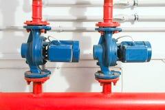 Sistema de calefacción en un cuarto de caldera bombas potentes rojas y tubo azul de los tubos Fotos de archivo libres de regalías