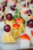 Sistema de canapes deliciosos con la fresa, la piña, el melón y la uva Foto de archivo