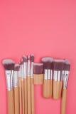 Sistema de cepillo del maquillaje en fondo en colores pastel rosado rojo Imagenes de archivo
