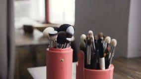 Sistema de cepillo para el maquillaje en la tabla en estudio Herramientas profesionales del maquillaje Un sistema de cepillos Art metrajes