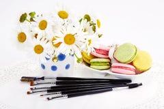 Sistema de cepillos del maquillaje con las flores y los macarrones Fotografía de archivo