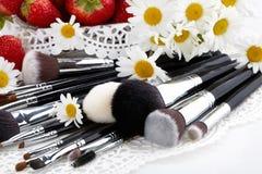 Sistema de cepillos del maquillaje con las fresas y las flores Foto de archivo libre de regalías