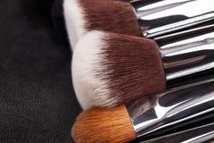 Sistema de cepillos del maquillaje en fondo de cuero negro Foto de archivo
