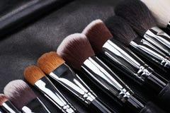 Sistema de cepillos del maquillaje en fondo de cuero negro Imágenes de archivo libres de regalías