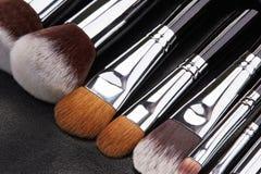 Sistema de cepillos del maquillaje en fondo de cuero negro Fotografía de archivo