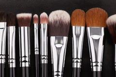 Sistema de cepillos del maquillaje en fondo de cuero negro Fotos de archivo libres de regalías