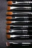 Sistema de cepillos del maquillaje en fondo de cuero negro Imagenes de archivo