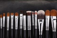 Sistema de cepillos del maquillaje en fondo de cuero negro Fotografía de archivo libre de regalías