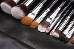 Sistema de cepillos del maquillaje en fondo de cuero negro Foto de archivo libre de regalías