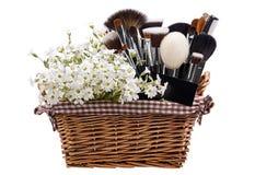 Sistema de cepillos del maquillaje en pesebre con las flores pamplina Aislado Wh Imagenes de archivo
