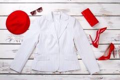 Sistema de chaqueta blanca femenina y de accesorios rojos Fotos de archivo libres de regalías