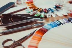 Sistema de clavos maravillosamente manicured en la mesa con las herramientas para la manicura Fotos de archivo