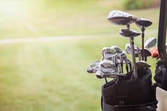 Sistema de clubs de golf sobre fondo verde del campo Fotografía de archivo libre de regalías