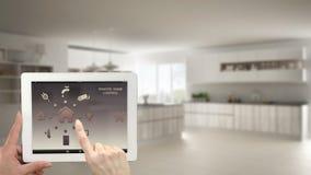 Sistema de controlo home remoto esperto em uma tabuleta digital Dispositivo com ícones do app Interior obscuro da cozinha minimal Imagens de Stock Royalty Free