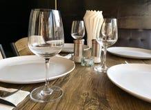 Sistema de copas de vino y de placas vacías en una mesa de comedor Imagen de archivo