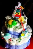 Sistema de cosas recién nacidas del bebé - torta hecha de los pañales en fondo oscuro fotos de archivo