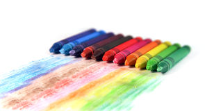 Sistema de creyones de cera multicolores con las rayas del dibujo en un blanco Imagen de archivo libre de regalías