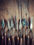 Sistema de cuchillos de paleta del artista en la tabla rústica de madera vieja, s retro Foto de archivo