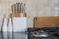 Sistema de cuchillos del cocinero en la encimera al lado de la tajadera y Foto de archivo libre de regalías