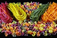 Sistema de diferentes tipos de pastas italianas coloridas, en un fondo negro, concepto sano de la comida, primer imagenes de archivo