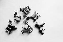 Sistema de diversas máquinas para el tatuaje en el fondo blanco negro Fotografía de archivo libre de regalías