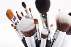 Sistema de diversos cepillos del maquillaje en el fondo blanco Imagenes de archivo