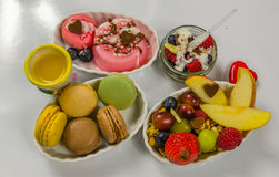 Sistema de diversos postres, macarons, fruta y pudines Foto de archivo libre de regalías