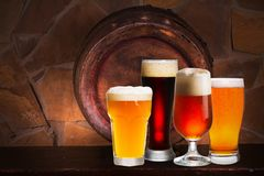 Sistema de diversos vidrios de cerveza en sótano, pub o restaurante Vidrios de cerveza, barril de cerveza viejo y pared de ladril Foto de archivo