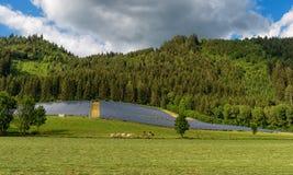 Sistema de energia de painel solar em um campo pela floresta Imagens de Stock