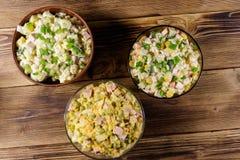 Sistema de ensaladas festivas de la mayonesa en la tabla de madera Imágenes de archivo libres de regalías