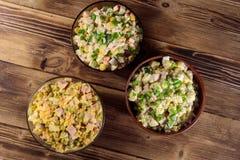 Sistema de ensaladas festivas de la mayonesa en la tabla de madera Imagen de archivo libre de regalías
