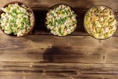 Sistema de ensaladas festivas de la mayonesa en la tabla de madera Fotos de archivo