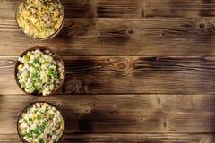Sistema de ensaladas festivas de la mayonesa en la tabla de madera Fotografía de archivo