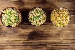 Sistema de ensaladas festivas de la mayonesa en la tabla de madera Visión superior Imagen de archivo libre de regalías