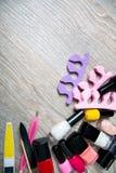 Sistema de esmalte de uñas y de herramientas para la pedicura de la manicura en un fondo de madera gris Capítulo Copie el espacio Fotos de archivo