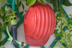 Sistema de extinção de incêndios da água com o capacete no jardim imagem de stock royalty free