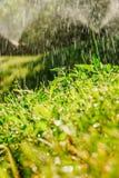 Sistema de extinção de incêndios automático do gramado do jardim na grama molhando da ação fotografia de stock royalty free