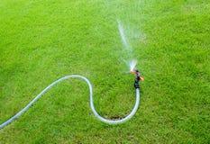 Sistema de extinção de incêndios que molha no jardim No gramado fotografia de stock royalty free