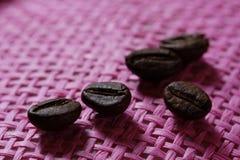 Sistema de granos de café macros asados frescos, fondo rosado de mimbre rosado Fotografía de archivo