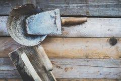 Sistema de herramientas usadas viejas de la albañilería en una superficie de madera áspera Imagenes de archivo