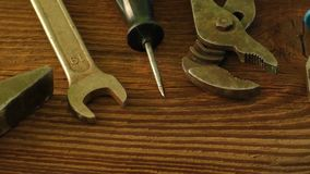 Sistema de herramientas viejas a reparar en una superficie de madera: martillo, alicates, llave, destornillador, tijeras almacen de metraje de vídeo