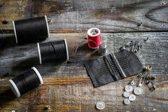 sistema de hilos de coser y de accesorios en fondo de madera Fotos de archivo