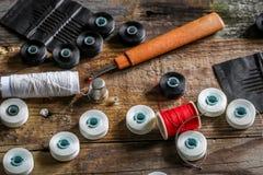 sistema de hilos de coser y de accesorios en fondo de madera Imagen de archivo libre de regalías