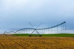 Sistema de irrigación de centro del pivote en campo marrón Imagenes de archivo