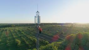 Sistema de la antena de la telecomunicación, técnico que trabaja encima de la antena celular en contraluz almacen de video