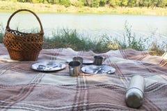 Sistema de la comida campestre, tres personas metal los cubiertos, termo, placas, tazas de té tela escocesa y servilleta marrones Fotografía de archivo libre de regalías