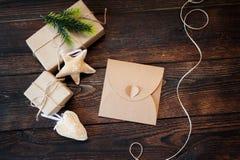 Sistema de la composición de la Navidad de las cajas de Kraft del regalo, de los juguetes de la materia textil y del bastidor del Fotografía de archivo